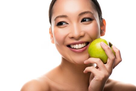 Smiling Asian woman holding fresh green apple, isolated on white background Stock Photo