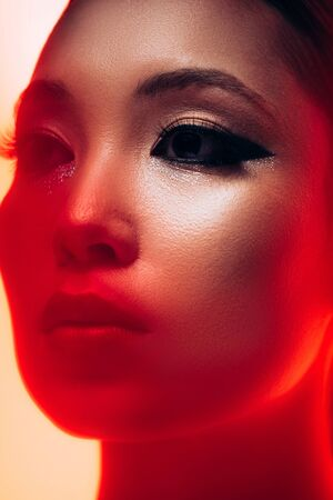 Close up of beautiful Asian girl with makeup in red light