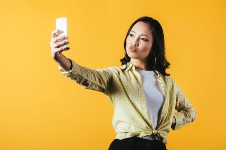 Attraktives asiatisches Mädchen, das selfie auf dem Smartphone lokalisiert auf gelbem Hintergrund nimmt Standard-Bild