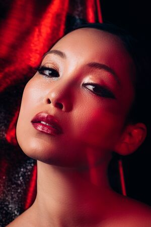 Seductive attractive Asian girl with makeup in red light Stock Photo