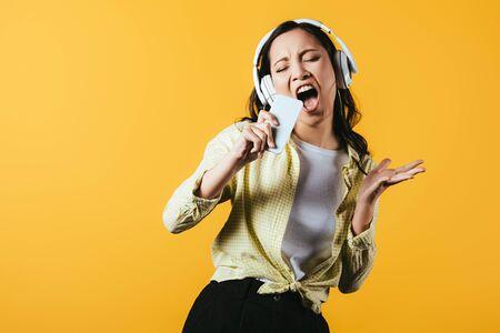 Atractiva chica asiática cantando y escuchando música con auriculares y smartphone, aislado sobre fondo amarillo Foto de archivo