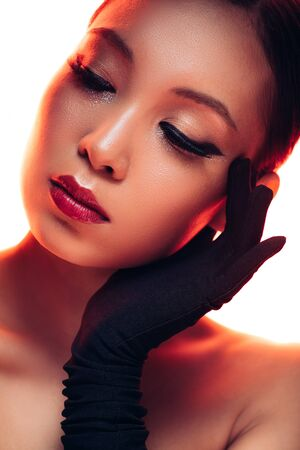 Tender Asian girl in black gloves with makeup in red light, isolated on white background