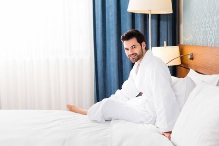 Happy bearded man looking at camera while sitting on bed in hotel room