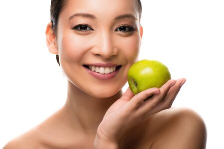 Cheerful Asian woman holding green apple, isolated on white background
