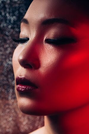 Close up of sensual Asian girl with makeup on closed eyes in red light Stock Photo