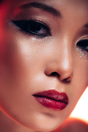 Beautiful Asian young woman in red light, toned picture