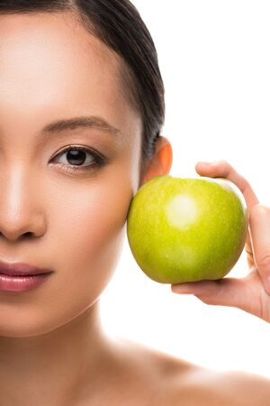 Attractive Asian woman holding green apple, isolated on white background