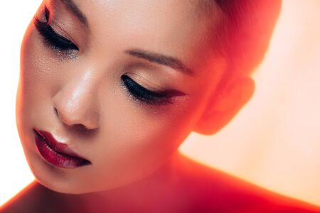 Beautiful Asian woman in red light, toned picture