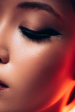 Close up of beautiful Asian girl in red light, toned picture