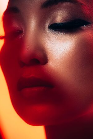 Close up of tender Asian girl with makeup in red light background