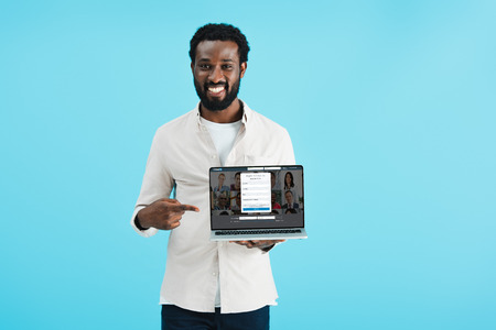 KYIV, UKRAINE - MAY 17, 2019: Smiling African American man pointing at laptop with linkedin website, isolated on blue background