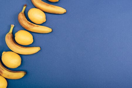 Top view of yellow lemons and bananas on blue background with copy space