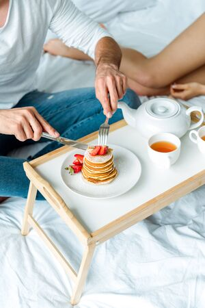 cropped view of man eating pancakes with strawberries and drinking tea in bed
