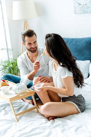 cheerful man feeding woman with cup in bed at morning