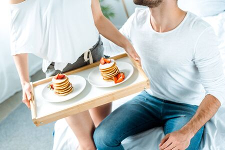 partial view of woman holding wooden tray with delicious pancakes and strawberries on plates near man Stock Photo
