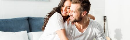 panoramic shot of happy smiling woman embracing man in bed at morning Stock Photo