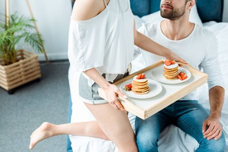 cropped view of woman holding wooden tray with delicious pancakes and strawberries on plates near man Stock Photo
