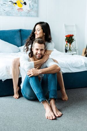 beautiful woman hugging happy barefoot boyfriend in bedroom Stock Photo