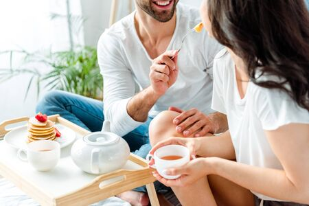 cropped view of cheerful man feeding woman with cup of tea in bed at morning