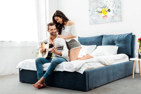 smiling man playing acoustic guitar near happy woman in bedroom Standard-Bild