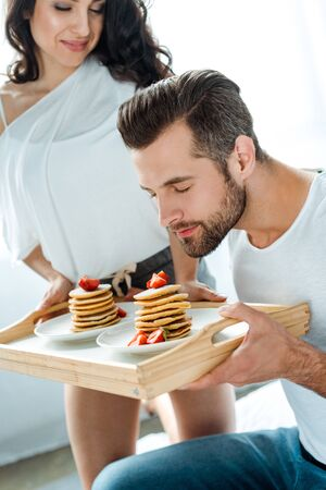 Young man smelling tasty pancakes with strawberries on wooden tray near smiling girlfriend Stock Photo