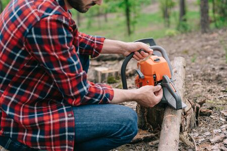 Cropped view of lumberjack in plaid shirt repairing chainsaw in forest