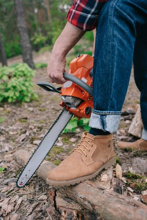 Cropped view of lumberjack in boots cutting tree trunk with chainsaw in forest Stockfoto