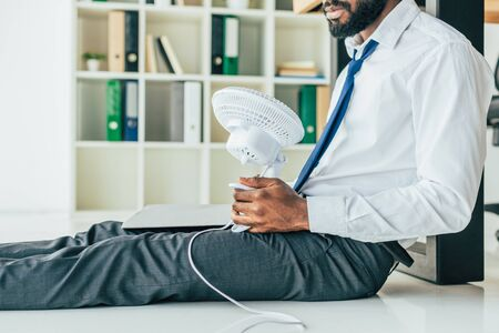 Cropped view of African American businessman sitting on floor and holding electric fan while suffering from heat in office Stock Photo