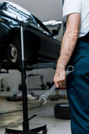Cropped view of repairman holding hand wrench in car repair station Stock fotó
