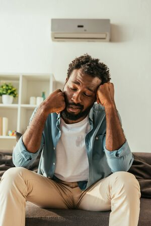 Tired African american man sitting on couch with closed eyes while suffering from heat Reklamní fotografie