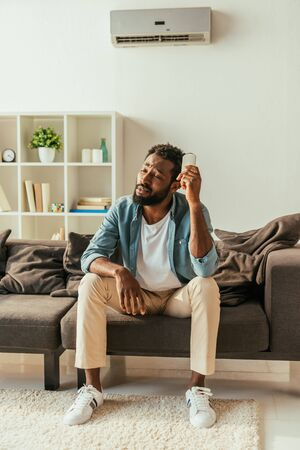 Exhausted African american man holding air conditioner remote controller while suffering from summer heat