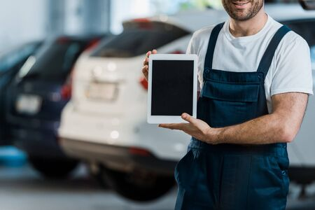 Cropped view of cheerful car mechanic holding digital tablet with blank screen