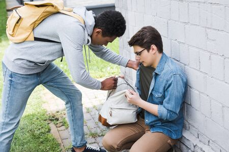 African american boy taking backpack from frightened boy in glasses