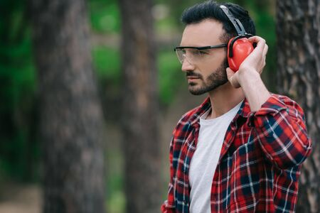 Pensive lumberjack touching noise-canceling headphones and looking away in forest