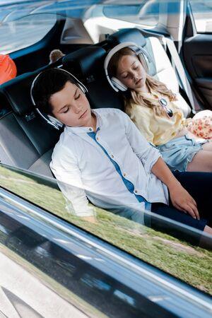 Selective focus of cute children in headphones sleeping in car 版權商用圖片
