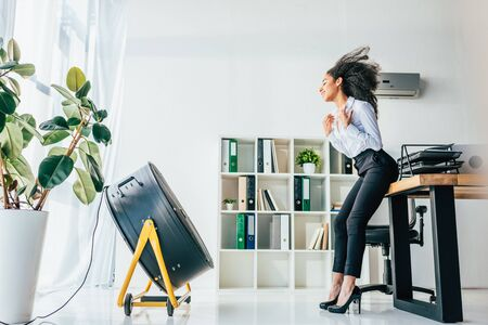 Smiling African american businesswoman standing in front of blowing electric ventilator in office Stock Photo