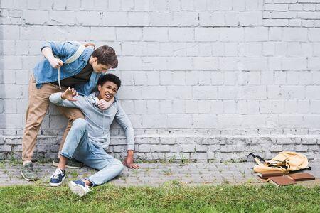 Chico agresivo en camisa bulling, va a golpear chico afroamericano en sudadera con capucha