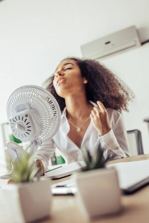 Selective focus of African american businesswoman holding electric fan while suffering from heat in office