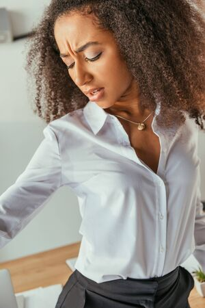 Dissatisfied African american businesswoman looking at sweaty shirt while suffering from summer heat