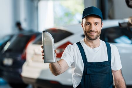 Happy car mechanic in cap holding bottle with car oil