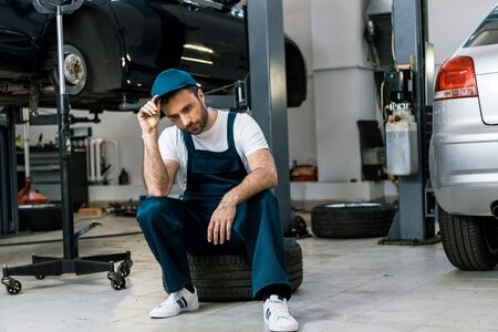 Upset bearded man touching cap and sitting on car tire
