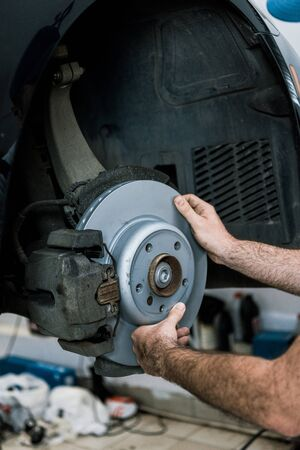 Cropped view of auto mechanic holding metallic car brake near automobile Stock fotó