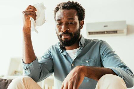 Unhappy African american man holding napkin while suffering from summer heat at home