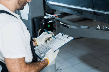 Ausgeschnittene Ansicht eines Automechanikers, der Zwischenablage und Stift hält
