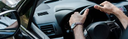 Panoramic shot of man holding steering wheel and driving automobile