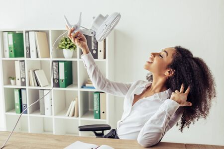 Cheerful African american businesswoman holding electric fan while suffering from heat in office
