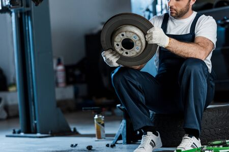 Cropped view of car mechanic holding metallic car brake while sitting on car tire