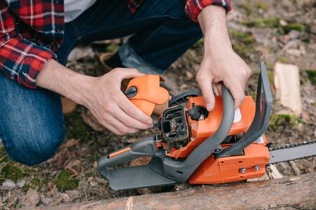 Cropped view of lumberer in plaid shirt fixing chainsaw in forest Stockfoto