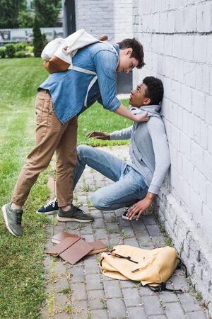 Aggressive boy in shirt bulling frightened African american boy in hoodie Reklamní fotografie - 127543290