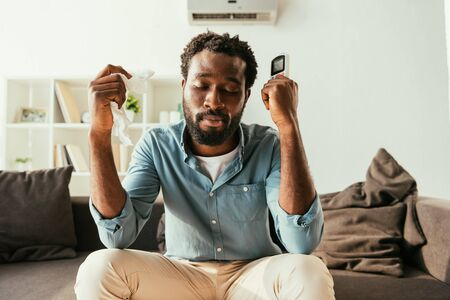 Exhausted African man holding napkin and remote controller while sitting on sofa and suffering from heat Reklamní fotografie